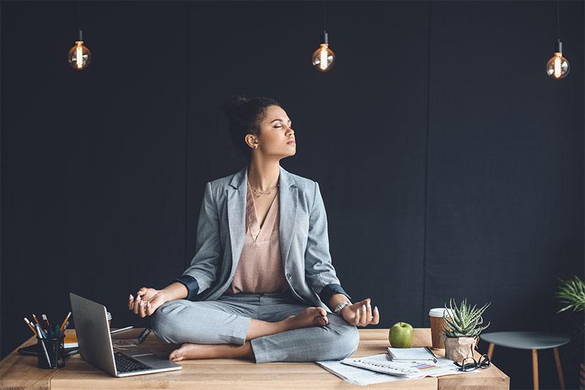 Geschäftsfrau, die im Büro auf dem Schreibtisch sitzt und meditiert. Meditation Wien.