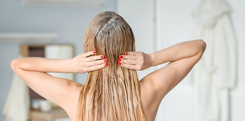 Junge blonde Frau, die mit dem Rücken zur Kamera steht, und eine Haarmaske gegen Schuppen aufträgt.