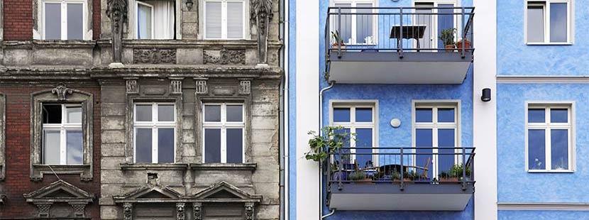 Fassaden von zwei gleichen Häusern, das eine saniert, das andere nicht. Altbausanierung Förderung Sanierungsscheck 2021.