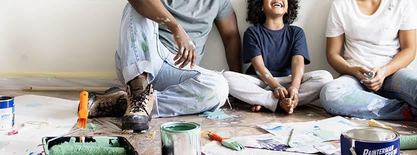 Junge Familie bei der Sanierung ihrer Wohnung, umgeben von Farbrollen und Tapetenresten. Altbausanierung Förderung Sanierungsscheck.