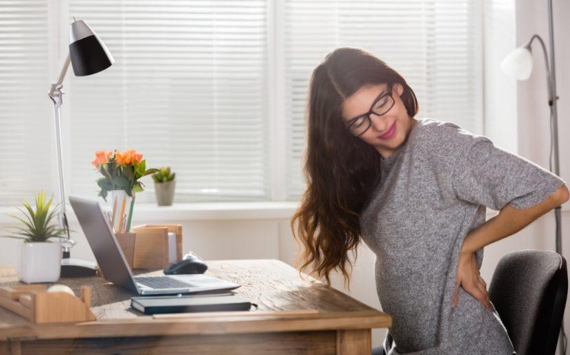 Junge Frau mit Rückenschmerzen, die durch einen Bandscheibenvorfall verursacht sind.