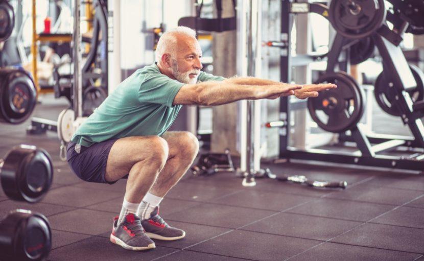 Älterer Mann, der einem erneuten Bandscheibenvorfall durch Kraftsport vorbeugt.