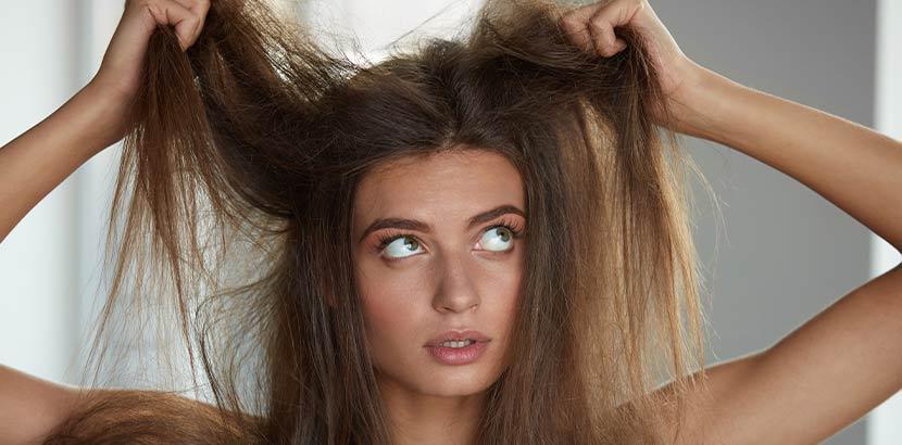 Junge Frau, die sich über ihren fliegenden Haare und den Frizz ärgert.