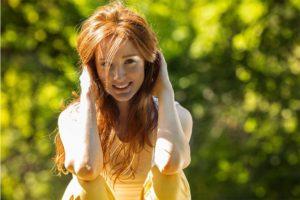 Junge Frau, die ihre Haare mit Henna gefärbt hat.