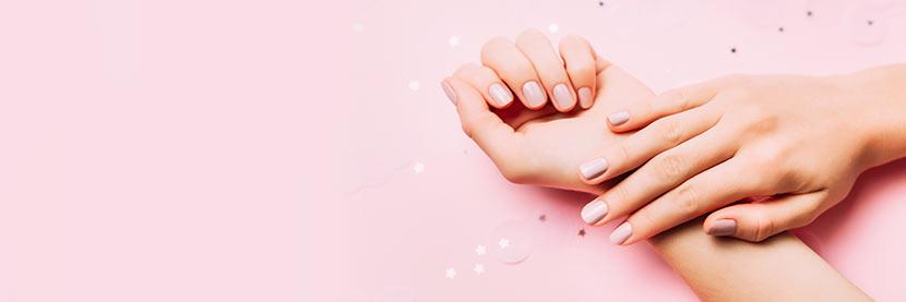 Shellac-Nägel: Zwei Hände mit rosa Shellac-Nägeln nach einer Maniküre.
