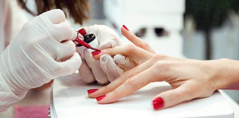 Eine Nageldesignerin kreiert bei der Maniküre rote Shellac Nägel