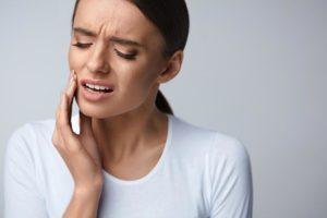 Eine Frau mit Schmerzen am Zahn vor der Behandlung möglicher Ursachen.
