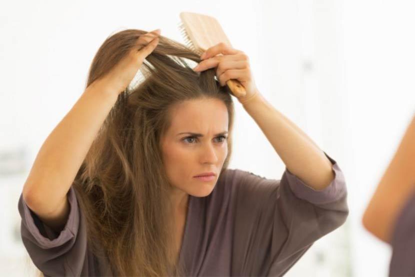 Junge dunkelhaarige Frau, die in ihren Haaren nach grauen Haaren sucht und sich fragt, was die besten Mittel gegen graue Haare sind.