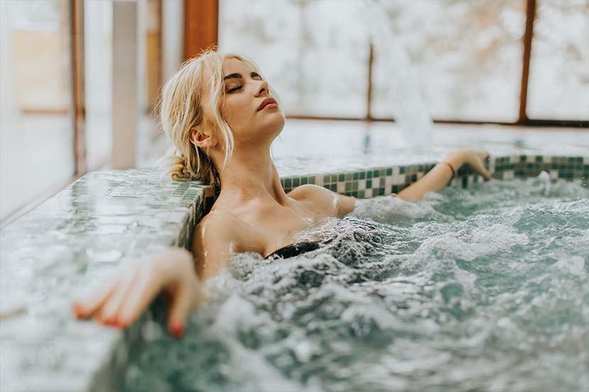 Junge blonde Frau, die sich in einem Whirlpool entspannt. Day Spa Wien.