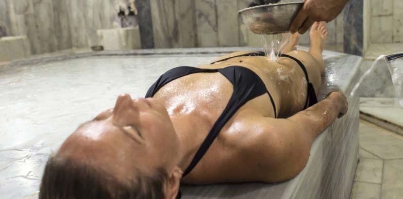 Junge hübsche Frau im Bikini, die in einem Hamam entspannt.