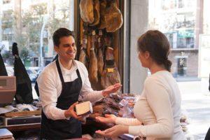 Freundlicher Verkäufer im Delikatessengeschäft, der eine Kundin berät. Feinkost Wien.