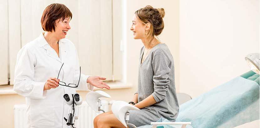 Junge Patientin bei einer Gynäkologin auf dem Behandlungsstuhl. Welcher Arzt wofür zuständig?