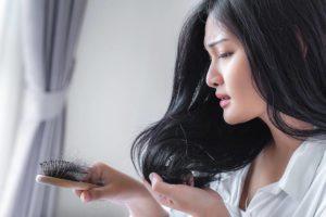 Junge Frau mit langen schwarzen Haaren, die erheblichen Haarverlust feststellt.