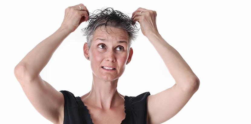 Frau im mittleren Alter, die ihr durch Haarausfall brüchig und dünn gewordenes Haar betastet.