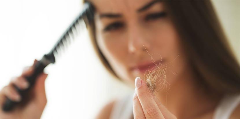 Junge Frau, die traurig auf die ausgefallenen Haare zwischen ihren Fingern schaut.