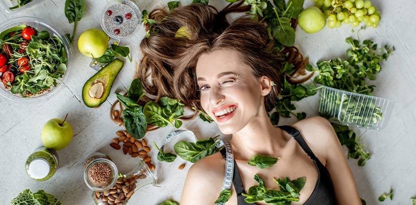 Junge hübsche Frau mit schönen Haaren, die inmitten von basischen Lebensmitteln liegt, die Haarausfall bei Frauen vorbeugen.