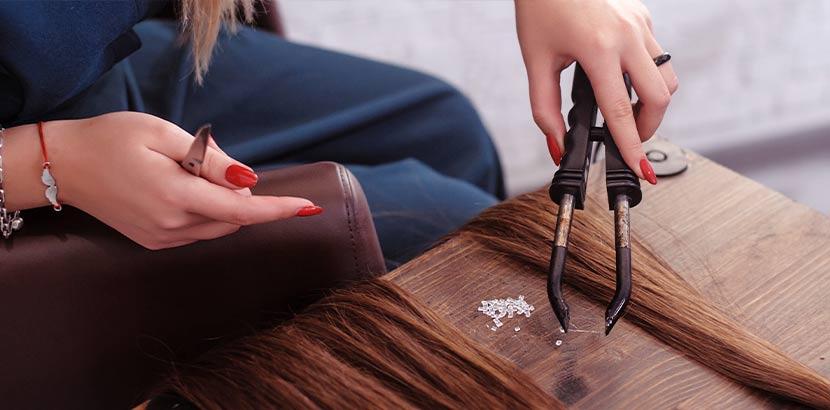 Junge Frau mit roten Fingernägeln, die Extensions mit Ringen vorbereitet. Haarverlängerung Wien.