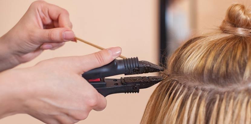 Hände einer Friseurin, die gerade Extensions einarbeitet. Haarverlängerung Wien.