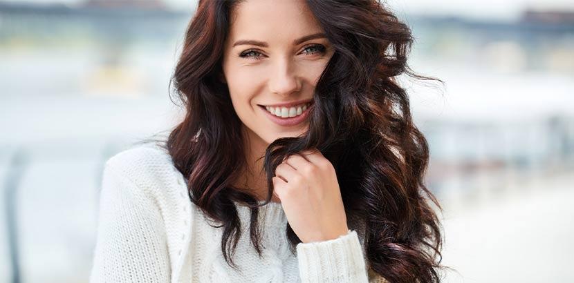 Junge Frau mit wunderschönen langen dunklen Haaren nach der Haarverlängerung Wien.