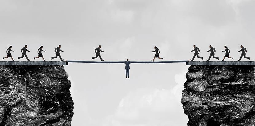 Mann, der zwischen zwei Klippen hängt und mit seinen Armen eine Brücke bildet für andere Männer, die auf diese Weise den Abgrund überqueren können. Versinnbildlicht die Mediation Wien.