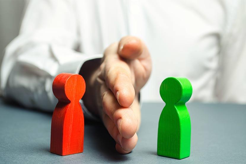 Männliche Hand, die zwischen einem grünen und einem roten Holzmännchen liegt und dadurch die Mediation Wien versinnbildlicht.
