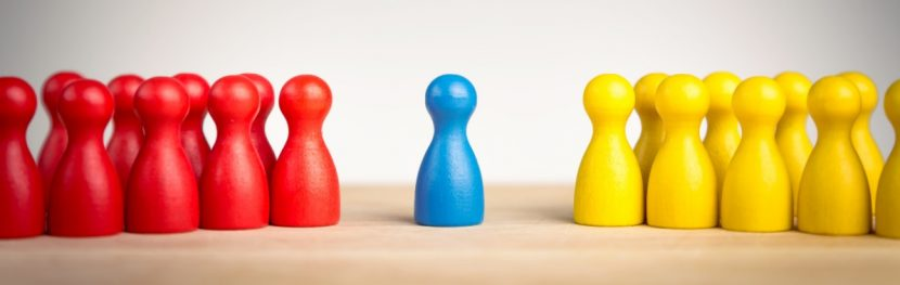 Blaue Figur, die zwischen einer Gruppe von gelben und einer Gruppe von roten Figuren steht und dadurch das Konzept einer Mediation versinnbildlicht.