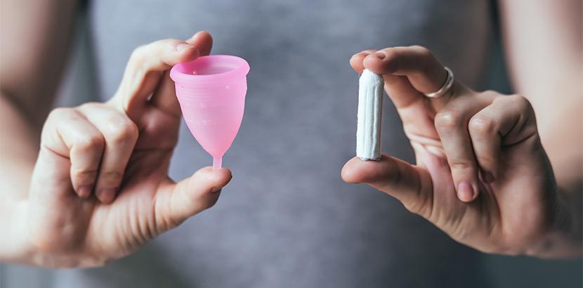 Eine Frau hält eine Menstruationstasse und einen Tampon.