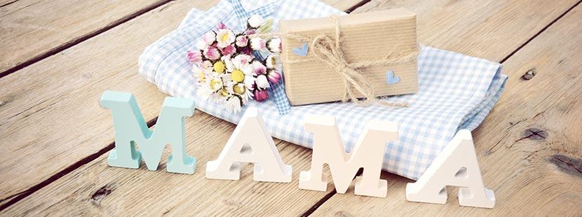 Muttertagsgeschenke: Holzbuchstaben, die Mama schreiben, Blumen und ein Geschenk zum Muttertag
