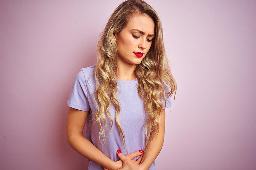 Schöne junge blonde Frau, die aufgrund von PCOS Schmerzen im Unterleib hat.