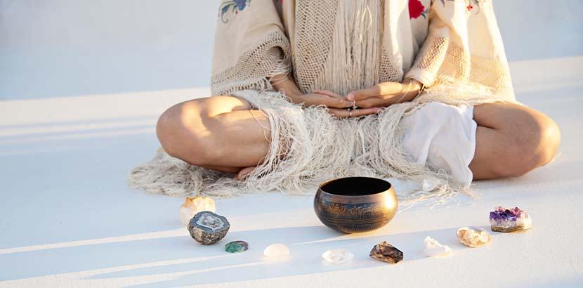 Junge Frau, die im Lotussitz vor einer Klangschale am Boden sitzt. Yoga Wien.
