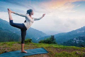 Junge hübsche Frau, die auf einer Almwiese mit Bergen im Hintergrund Yoga macht. Yoga Wien.