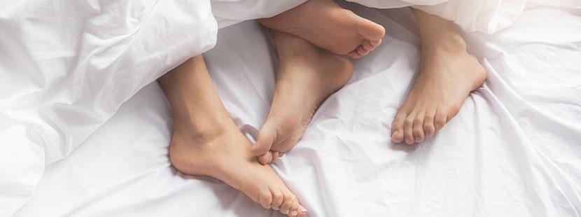 Füße eines Paares, das zusammen unter der Bettdecke liegt und über eine HPV Impfung spricht.