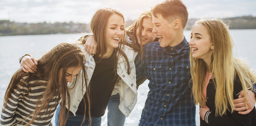 Gruppe von Jugendlichen, die am Strand miteinander gerumalbern. Jungen und Mädchen. HPV Impfung.