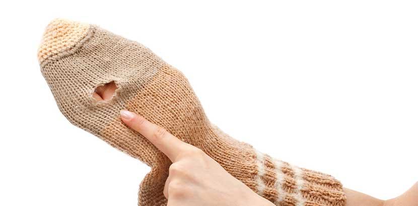 Frauenhände, die ein Loch in einer Wollsocke herzeigen. Der Grund, warum man Kleidermotten bekämpfen muss.