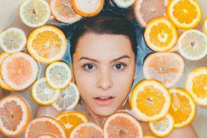 Frau schwimmt in Wasser mit Zitronenscheiben