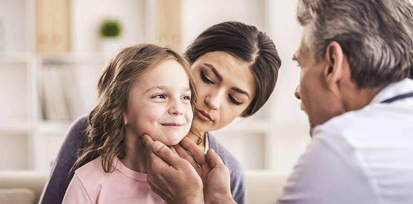 Älterer Hausarzt, der die Lymphknoten eines kleines Mädchens abtastet. Hausarzt Wien.