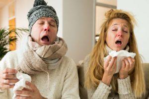Ein Mann und eine Frau, die beide eine schlimme Erkältung haben und zum Hausarzt müssen. Hausarzt Wien.
