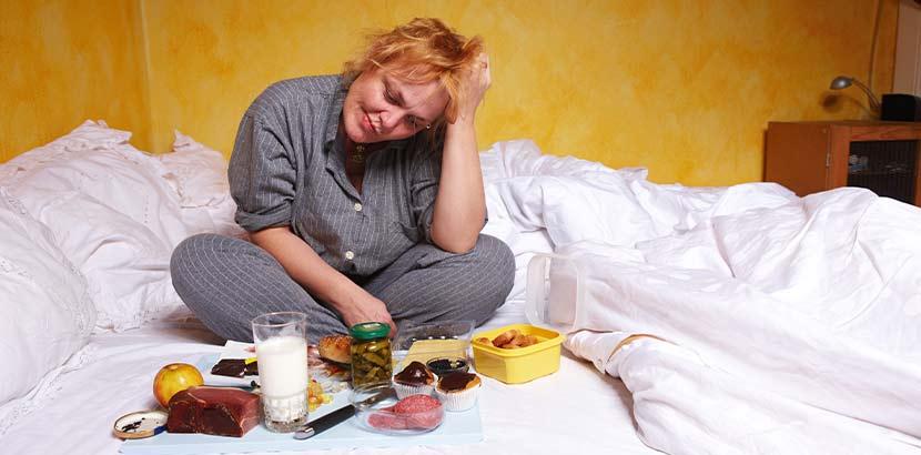 Übergewichtige Frau, die im Bett sitzt und eine Fressattacke hat. Magenballon Kosten Österreich