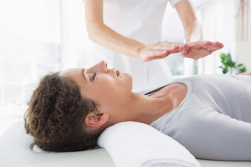 Junge Frau bei der Reiki Behandlung, auf dem Rücken liegend.