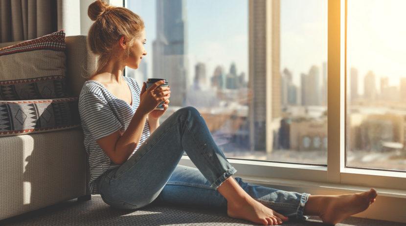 junge barfüßige Frau mit Dutt genießt Ausblick vor einem Schallschutzfenster