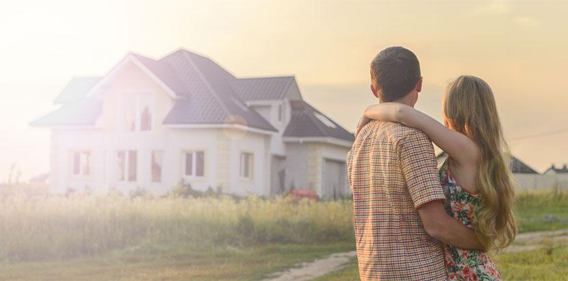 Junges Pärchen, das mit dem Rücken zur Kamera steht und schwärmend auf ein Haus blickt, das sie kaufen möchten.