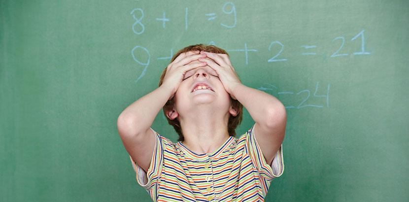 Junge, der an einer Tafel, an der Zahlen stehen, verzweifelt. Dyskalkulie.