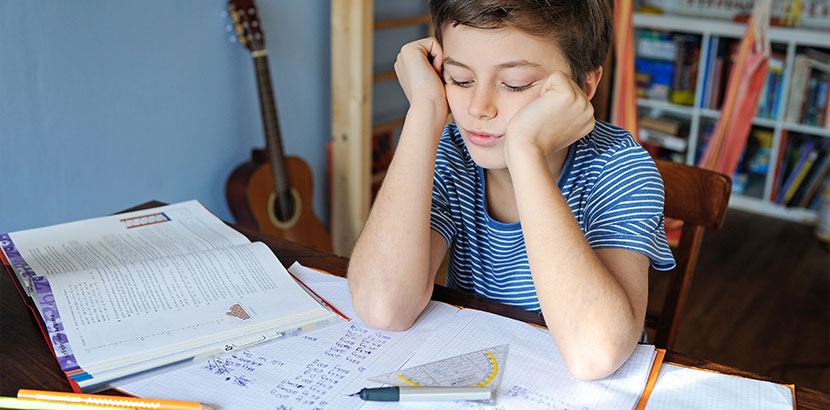 Junge mit Dyskalkulie sitzt unglücklich über seinen Matheaufgaben.