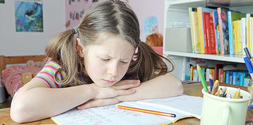 Kleines Mädchen mit Dyskalkulie sitzt unglücklich über ihren Matheaufgaben.