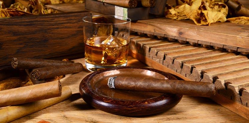 Zigarre und ein Glas Whiskey auf einem schönen Holztisch; das perfekte Geschenk für Männer.
