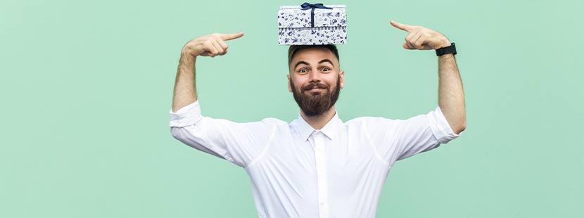 Bärtiger Mann vor grünem Hintergrund, der mit den Fingern auf ein Packerl zeigt, das auf seinem Kopf liegt. Geschenke für Männer, Männergeschenke.