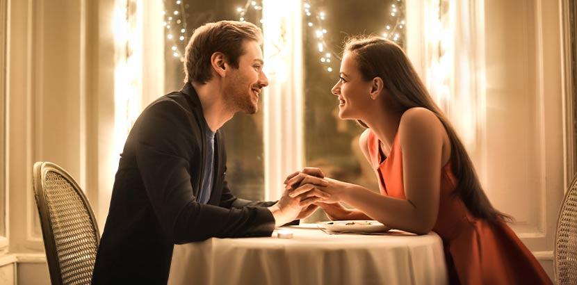 Attraktives Paar, das in einem romantischen Restaurant beim Dinner sitzt. Geschenke für Männer.