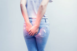 Rückenansicht einer jungen Frau, die sich den Po hält, weil sie Schmerzen hat. Hämorrhoiden Behandlung in Wien.
