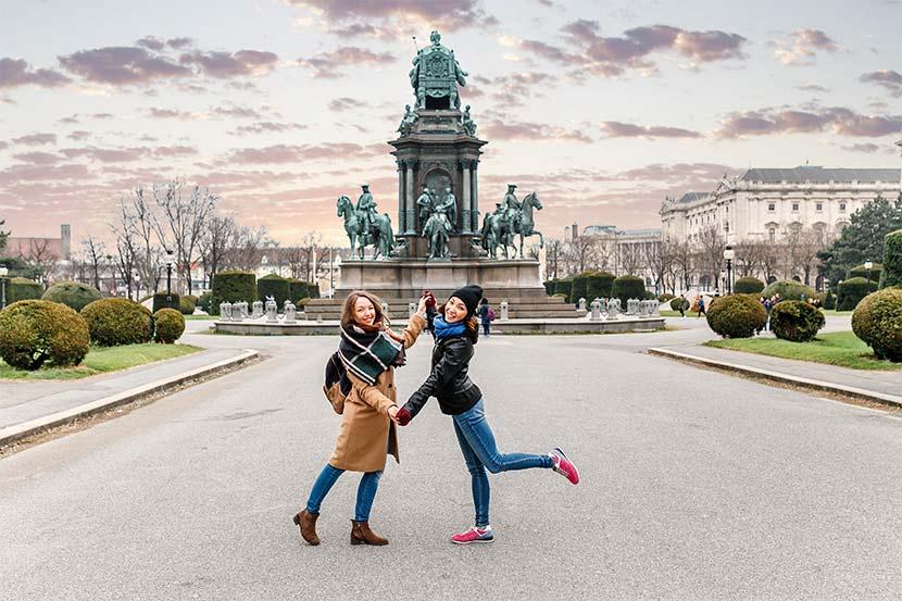 Zwei Freundinnen, die sich im herbstlichen Wien umarmen.