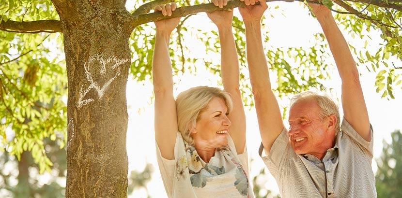 Älteres Paar, das sich mit den Händen an einem dicken Ast festhält und einander anlächelt. Wechselbeschwerden lindern.